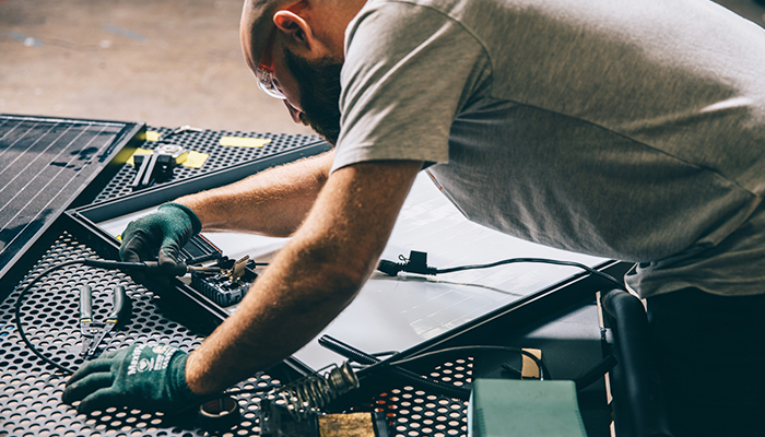 Man focuses on electrical wiring and soldering task.
